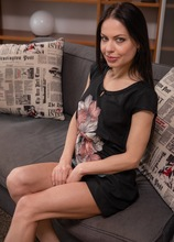 Dark haired MILF Allatra Hot wearing only heels on the sofa.